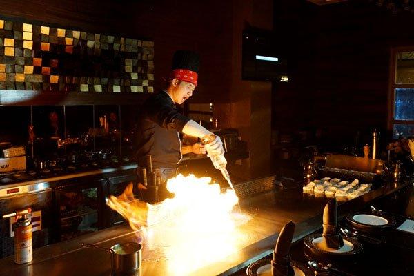 Một đầu bếp của nhà hàng thương hiệu Lion City tại TPHCM đang thực hiện các món ăn cho thực khách - Ảnh: Lê Hoàng