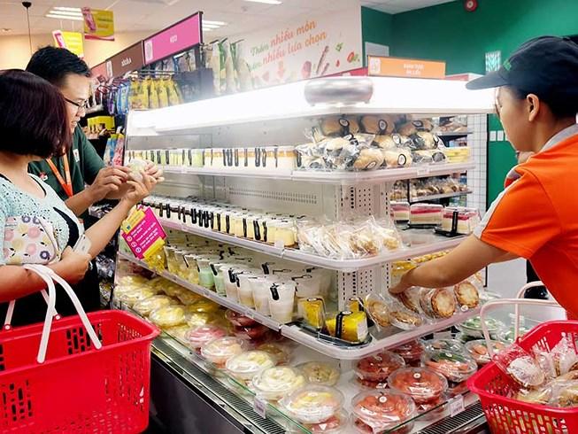 Các món ăn vặt rất được người Việt ưa chuộng. Trong ảnh: Khách hàng đang tự tay hâm nóng thức ăn bằng lò vi sóng có sẵn ở  cửa hàng tiện lợi. Ảnh: TÚ UYÊN