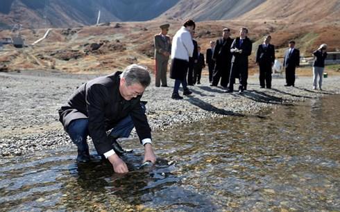 Ông Moon Jae-in lấy đầy chai nước hồ Cheonji. (Ảnh: Reuters)