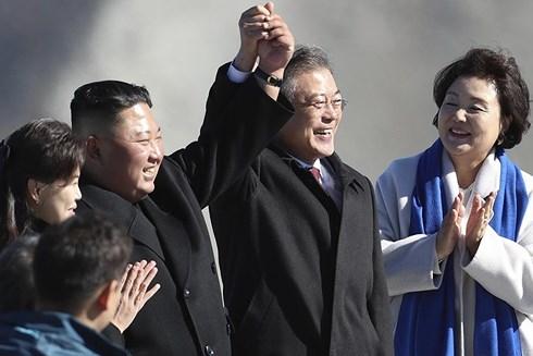 Nhà lãnh đạo Triều Tiên Kim Jong-un (trái) và Tổng thống Hàn Quốc Moon Jae-in nắm tay nhau trên đỉnh Peakdu. (Ảnh: AP)